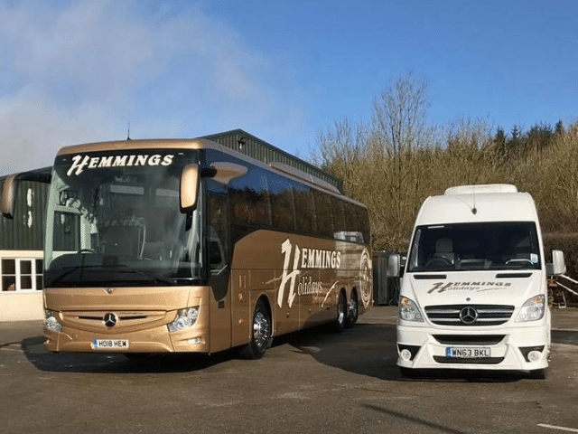 A gold coloured coach parked next to a white minibus
