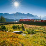 a train travelling in front of mountains and blue sky