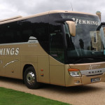 gold Hemmings coach holidays bus parked in front of buildings